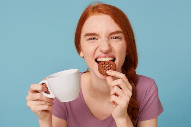 Primo piano di una bella bella ragazza dai capelli rossi che sorride giocosamente guardando la fotocamera, tiene in mano la tazza bianca con la bevanda