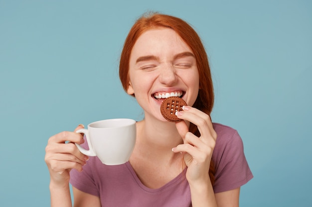 Close up of a lovely beautiful red-haired girl with closed eyes,feels pleasure, keeps in hand white cup with drink