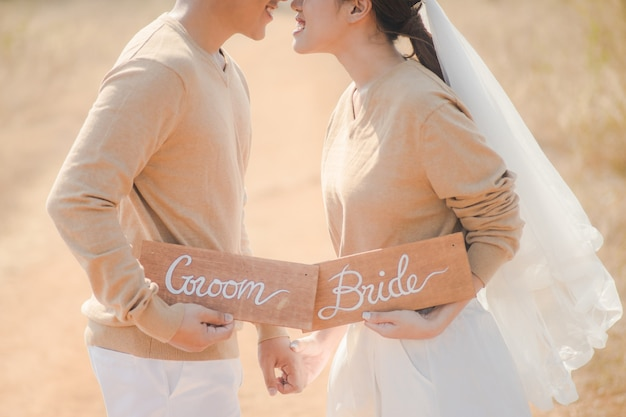Close up of lovely bride and groom holding sign wooden plate outdoors. romantic couple and love concept