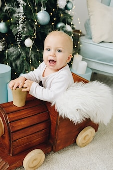 Close up of a lovely caucasian baby sitting in a wooden toy train near decorated christmas tree