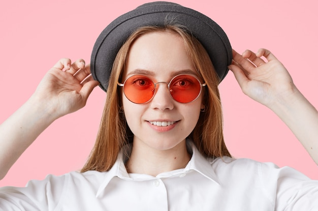 Close up lovely delighted female with pleasant smile, wears stylish red sunglasses and black hat, isolated on pink. fashionable teenager going for walk during weekend