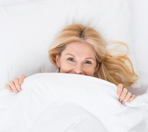Close-up lovely mature woman smiling in bed