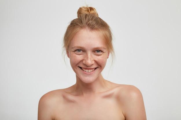 Primo piano di bella giovane femmina positiva con acconciatura casual guardando allegramente e sorridendo piacevolmente, in posa sul muro bianco con spalle nude