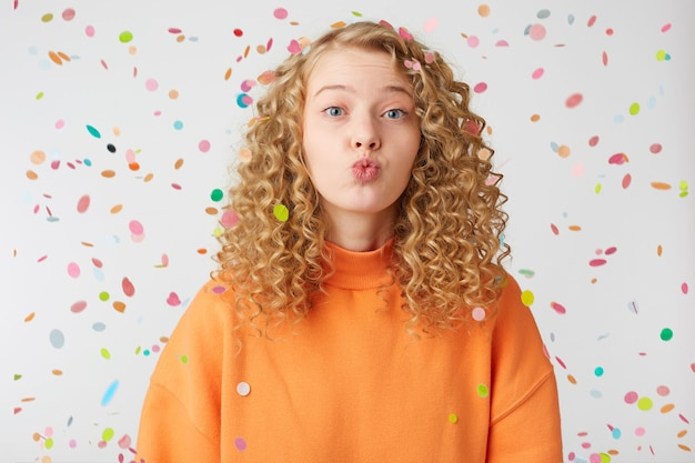 Close up of lovely sweet nice blonde girl sending air kiss directly to the front with tender look, stands under falling confetti