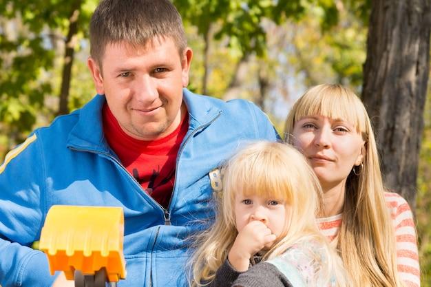 公園で一人の子供と一緒に素敵な白い家族をクローズアップ。カメラを見て