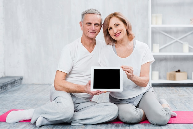 Close-up of a loving couple holding black screen digital tablet
