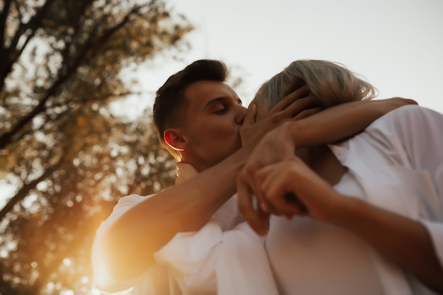 Close up of loving couple is kissing. man is touching face of girlfriend with tenderness in summer evening.