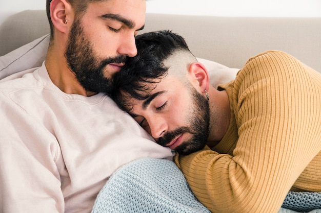 Close-up of loving gay couple sleeping together