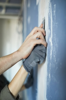 Close up of loving young couple smoothing dry wall while renovating house together, copy space
