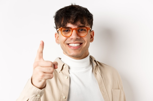 Primo piano di un bell'uomo fortunato con gli occhiali, sorridente e puntato il dito verso la telecamera, lodando qualcosa di buono, in piedi su sfondo bianco.