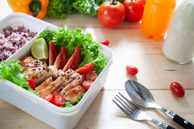 Close up of lunch box, grilled chicken breast with lettuce, tomato and rice berry.