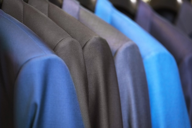 Close up luxurious style gentlemen suit row, hanging in a closet.