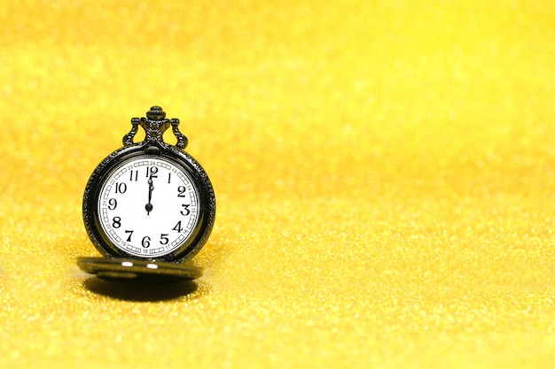 Close up of luxury pocket watch on glitter background with copy space