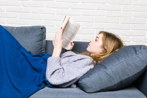 Close up of lying teen girl reading book relaxing at home