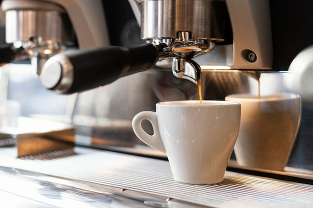 Close up machine pouring coffee in cup