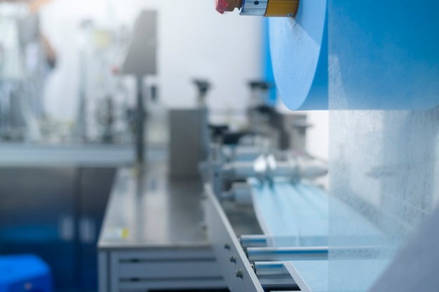 Close up of machine producing surgical mask in modern factory, covid-19 protection and medical concept.