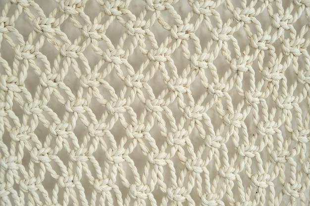 Close-up of macrame handmade, decorative panel woven from light cotton ropes on the wall, abstract texture background