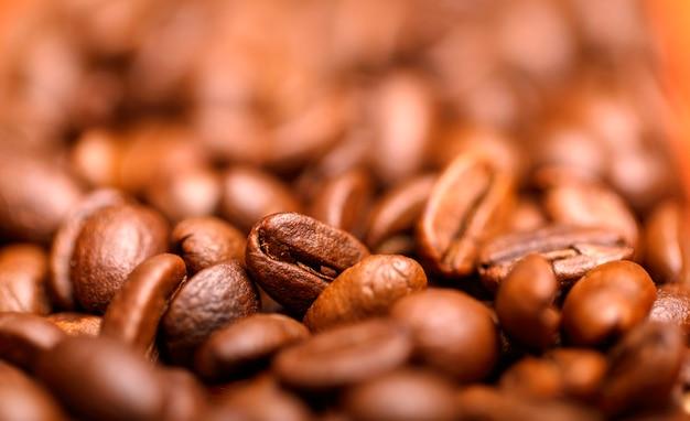 クローズアップマクログループローストブラウンまたはブラックコーヒーの穀物の背景。コーヒー豆を閉じます。