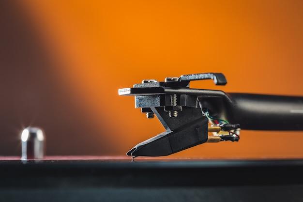 ヴィンテージアナログハイファイステレオビニールターンテーブルのトーンアームのフォノカートリッジにマクロ写真をクローズアップします。