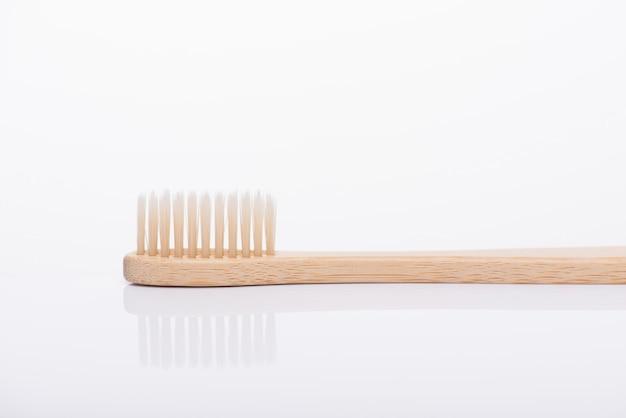 白い背景で隔離の環境に優しいベージュ色の歯ブラシのクローズアップマクロ側面プロファイルビュー写真