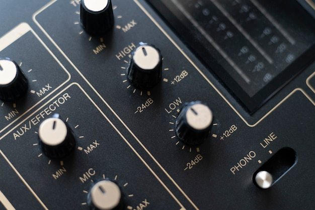 A close up macro sound mixer controller with adjustable knobs and faders