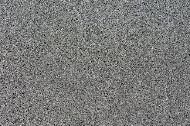 Close-up macro view of black color volcanic sand surface. detailed nature background or pattern texture taken in natural environment. weathered many years, inimitable, unique effect to textured design