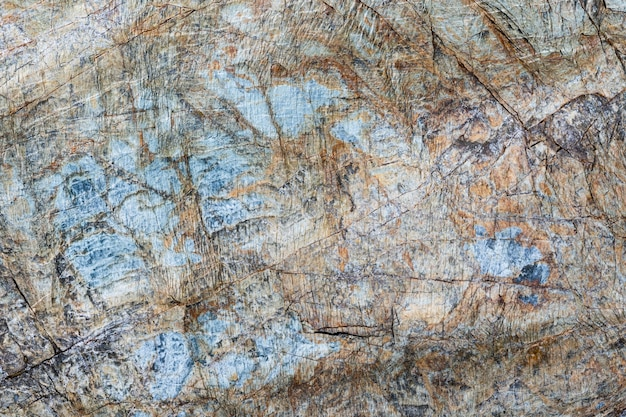 Close-up macro view of cracked stone surface brown, grey, blue color. detailed nature pattern texture, background taken in natural environment. weathered over years, inimitable effect textured design.