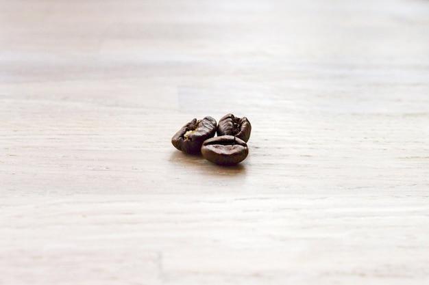 木製のテーブルの上の3つの焙煎コーヒー豆のマクロビューを閉じます。選択的なソフトフォーカス。テキストコピースペース。