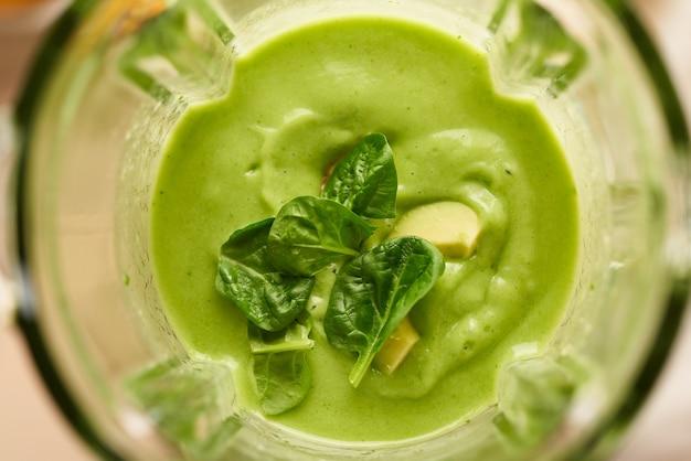Крупным планом макрос, взбивая смесь фруктов и овощей в блендере, готовит веганский зеленый смузи