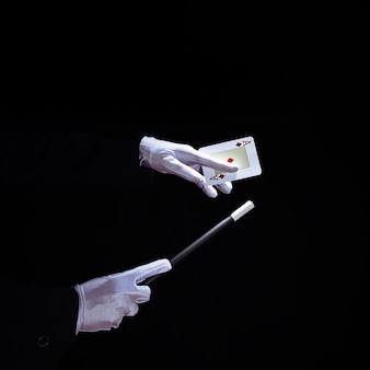 Close-up of magician performing trick on playing card with magic wand