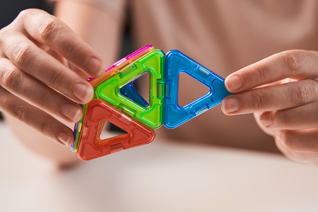 Close up of magnetic building toy. woman playing with preschooler.