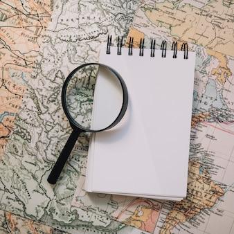 Крупным планом увеличительное стекло и ноутбук на карте