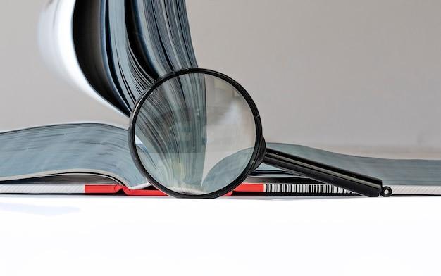 Закройте увеличительное стекло и техническую книгу с концепцией образования инженера переворачивания страниц