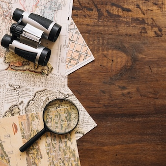 Close-up magnifying glass and binoculars on maps