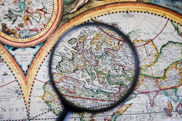 Primo piano della lente d'ingrandimento sopra la mappa antica colorata