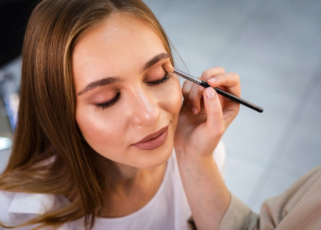 Close up make-up artist applying nude eyeshadow on woman with brush