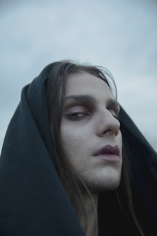 Close-up make-up male witch with black hood
