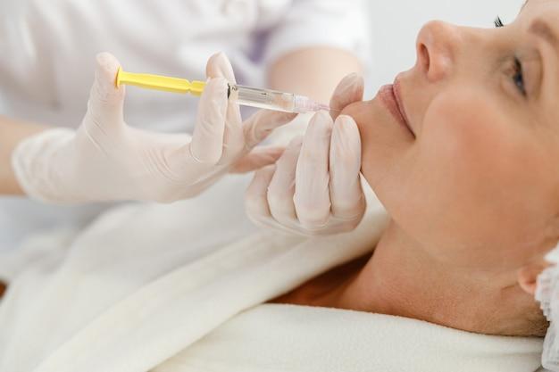 Крупным планом делает уколы мезотерапии пожилой женщине.