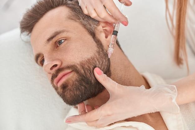 Крупным планом делает уколы мезотерапии бороду мужчине. лечение мужского косметолога для роста волос.