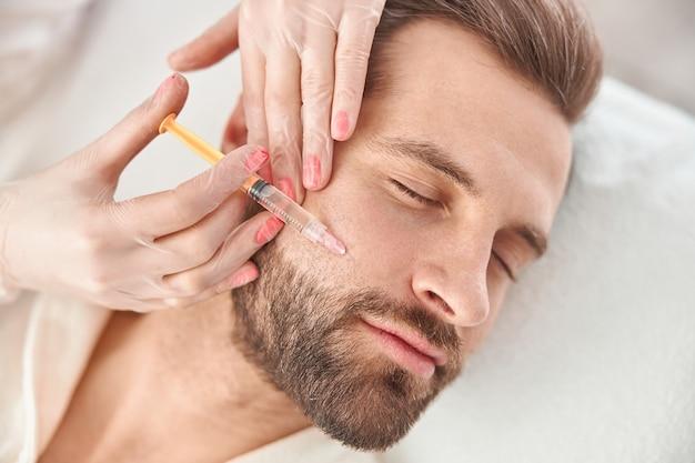 Крупным планом делает уколы мезотерапии молодому человеку. процедура косметолога для мужчин для подтяжки и разглаживания морщин на коже лица.