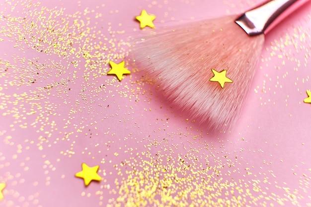 Крупным планом кисть для макияжа и блестящие блестки на розовой поверхности