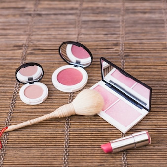 Close-up of makeup brush; lipstick and blusher on placemat
