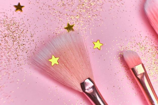 Крупным планом кисти для макияжа и блестящие блестки на розовой поверхности