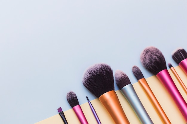 Close-up of makeup brushes on blue backdrop