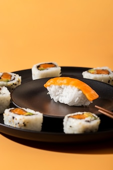 Close up maki sushi rolls with nigiri on yellow background