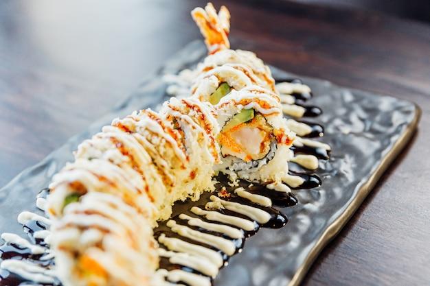Close-up maki sushi with rice, shrimp tempura, avocado and cheese inside covered crispy tempura flour. topping with teriyaki sauce and mayonnaise.