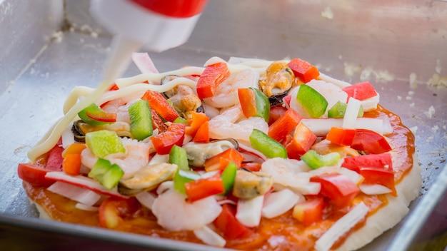 Close up making pizza with sea food, shrimp, shellfish