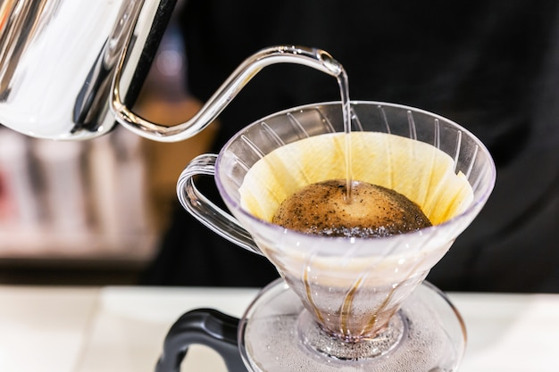 Close-up making pour-over coffee with alternative method called dripping. coffee grinder, coffee stand and pour-over on marble top counter.