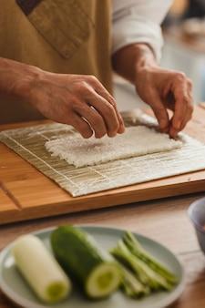 대나무 매트 아시아 음식 배달에 롤링을 위해 쌀을 준비하는 초밥 남성 손을 만들기를 닫습니다