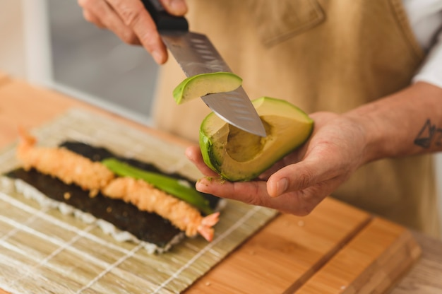 스시 재료를 준비하는 균일한 껍질을 벗긴 아보카도로 스시 과정 요리사 만들기